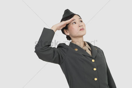 Respect : Serious female us military officer saluting over gray background