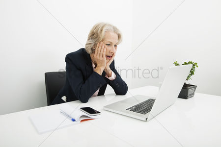Office worker : Shocked senior businesswoman using laptop at desk in office