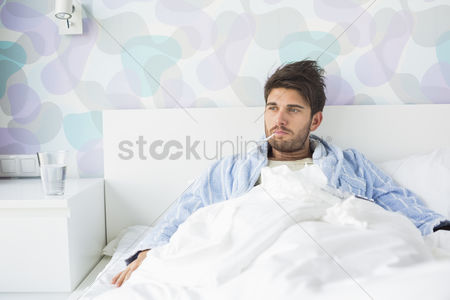 Thermometer : Sick man with thermometer in mouth reclining on bed at home