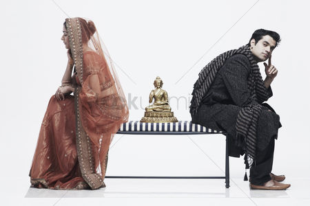 Sculpture : Side profile of a newlywed couple sitting on opposite ends of a bench with a statue of buddha between them