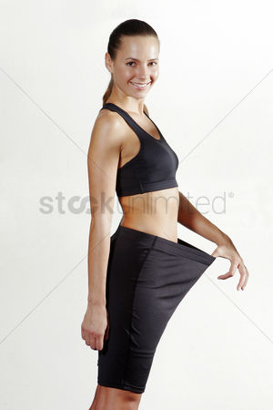 Body : Side shot of a lady pulling her loose pants