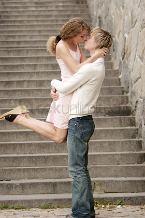 Kissing : Side shot of a man lifting up his girlfriend while kissing