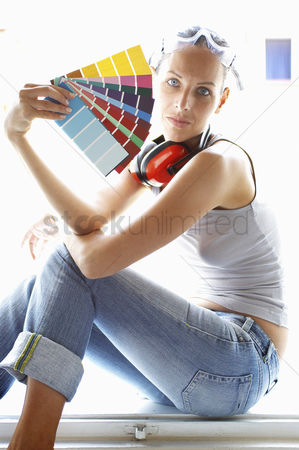 Selection : Side shot of a woman with headphone and goggles holding colour cards