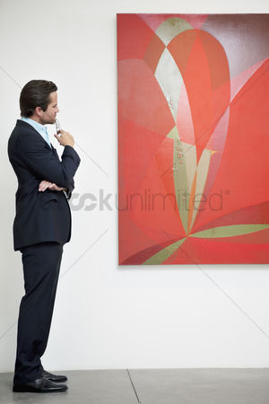 Interior background : Side view of a man looking intensely towards painting