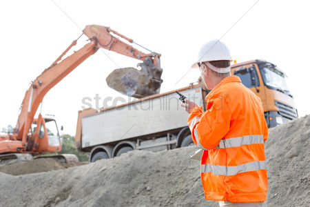 Supervisor : Side view of architect using walkie-talkie while working at construction site