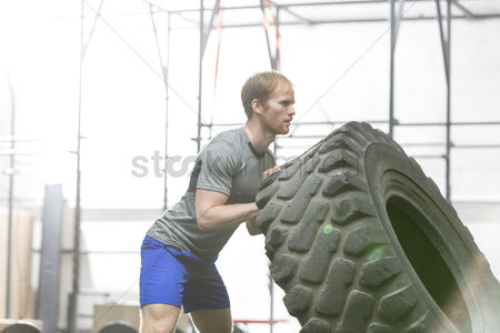 Strong : Side view of dedicated man flipping tire in crossfit gym