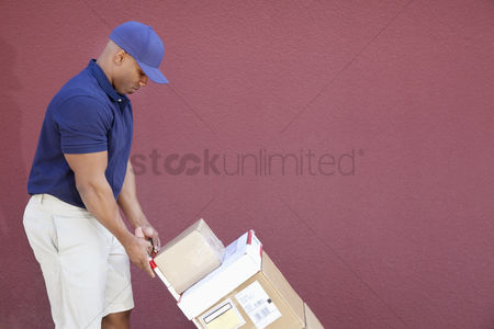 Pushing : Side view of muscular african american delivery man with handtruck