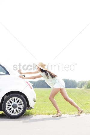 Pushing : Side view of woman pushing broken down car on country road