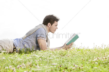 Grass background : Side view of young man reading book while lying on grass against clear sky