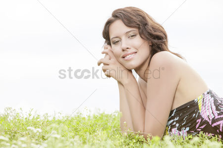 Grass background : Side view portrait of young woman lying on grass against clear sky