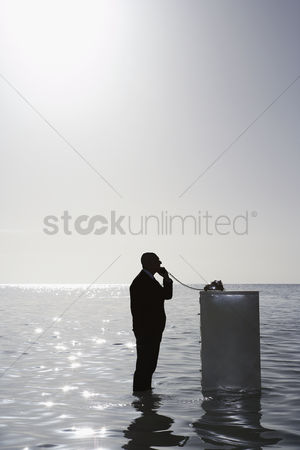 Pocket : Silhouette of business man using phone on filing cabinet in sea side view elevated view