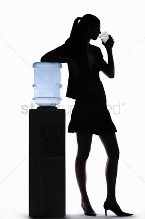 Well being : Silhouette of businesswoman drinking water