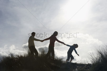 Grass : Silhouette of parents and daughter  5-6  holding hands on sand dunes
