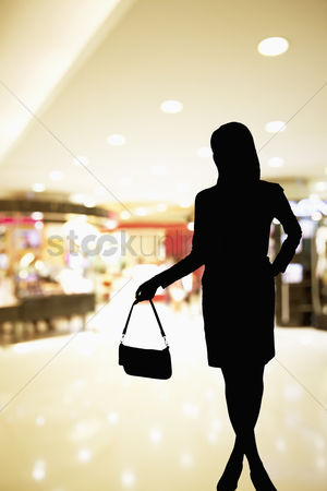 Spending money : Silhouette of woman standing in a shopping mall ad holding a purse