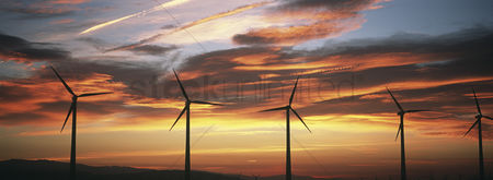 Moody : Silhouettes of wind turbines at sunset