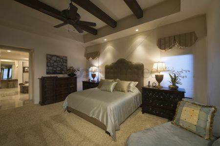 Interior : Silk bed cover on double bed in palm spring bedroom with beamed ceiling