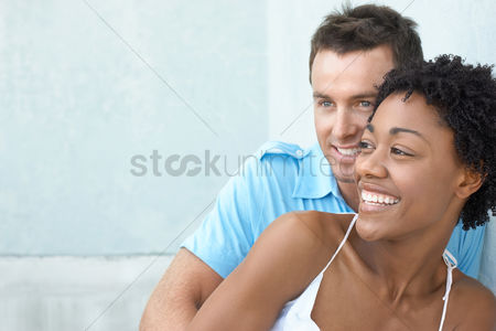 Two people : Smiled couple standing together against wall portrait