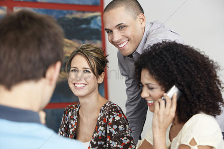 Cell phone : Smiling businesspeople listening to colleague in meeting  using cell phone in meeting