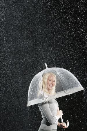 Black background : Smiling businesswoman standing under umbrella during rain