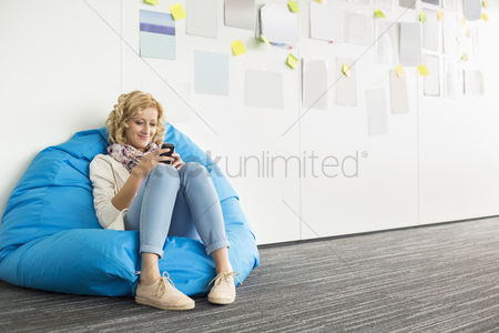 Businesswomen : Smiling businesswoman using mobile phone on beanbag chair in creative office