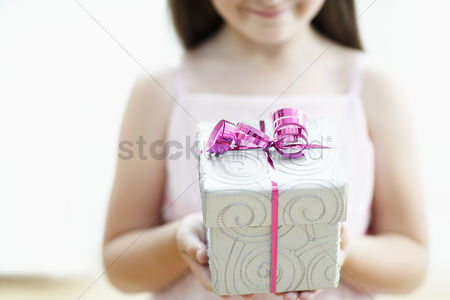 Celebration : Smiling girl with gift mid section close up
