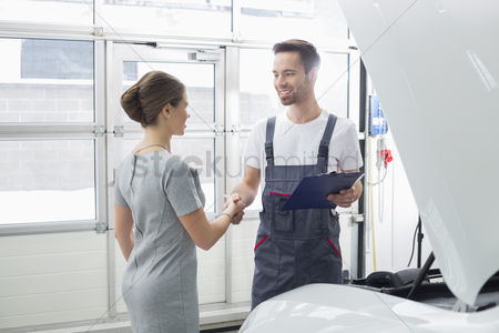 Assistance : Smiling maintenance engineer shaking hands with female customer in car repair shop