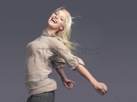 Blowing : Smiling woman standing arms outspread side view