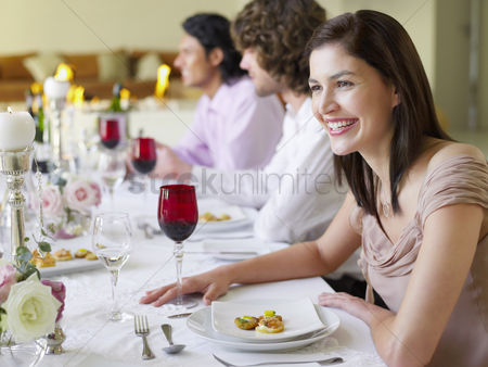 Appearance : Smiling young woman at dinner party