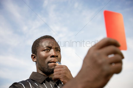Blowing : Soccer referee holding out red card and blowing whistle portrait