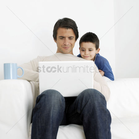 Three quarter length : Son watching father using laptop