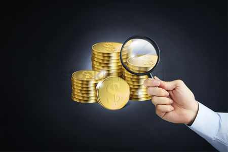 Magnifying glass : Stack of coins with a hand holding magnifying glass