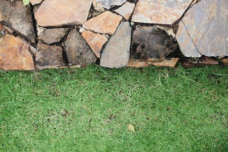 Grass background : Stone wall and fresh green grass