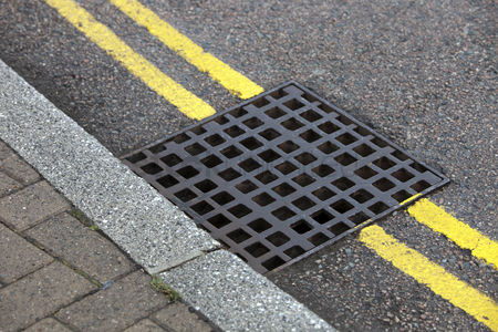 England : Street drain over double yellow line on street