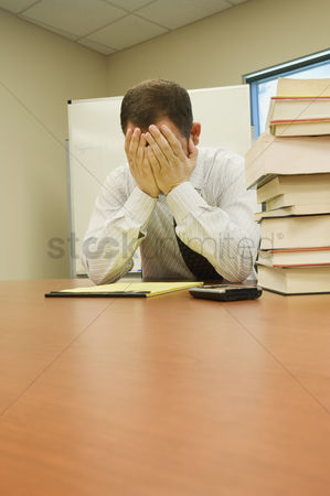 Notepad : Stressed businessman with head in hands