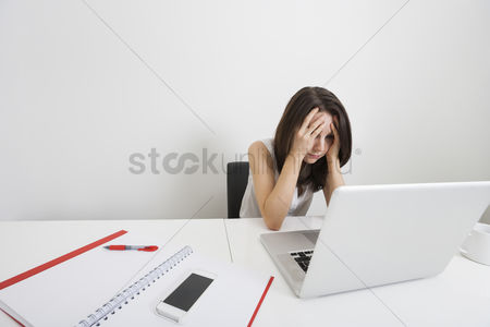 Businesswomen : Stressed businesswoman with laptop at desk in office