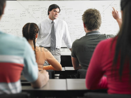 High school : Students talking to teacher in classroom