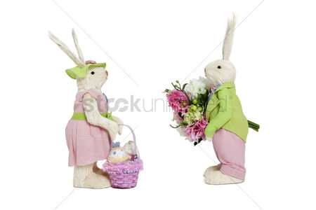 Animal : Stuffed toys portrayed as male with flowers and female with basket over white background