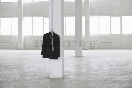 Spacious : Suit jacket hangs on pillar in empty warehouse