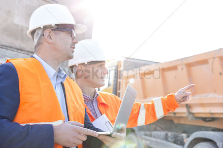Supervisor : Supervisor showing something to colleague holding laptop at construction site