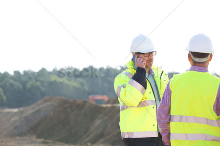 Supervisor : Supervisor using mobile phone while standing with colleague at construction site against clear sky