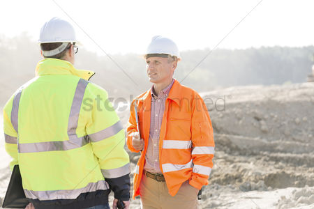 Supervisor : Supervisors discussing at construction site on sunny day