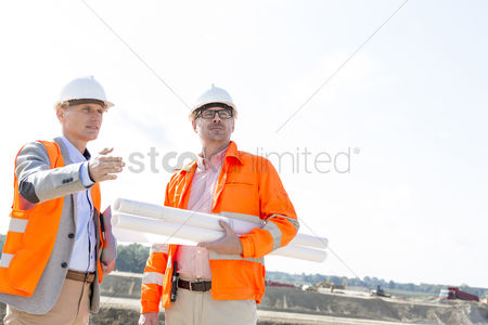 Supervisor : Supervisors with blueprints discussing at construction site against clear sky