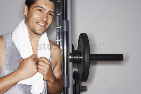 Club : Sweaty man with towel  by weight machine after workout