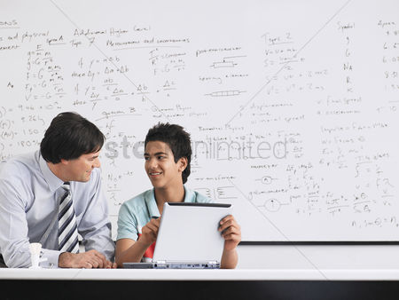 Eastern european ethnicity : Teacher and student using laptop sitting in physics classroom