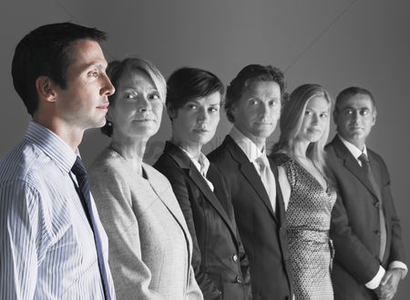 Leadership : Team of professionals looking at colleague against gray background