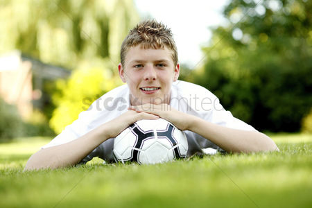 Lying forward : Teenage boy lying forward on the field with his chin resting on football
