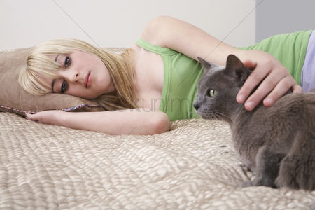 Contemplation : Teenage girl  16-17  lying on bed with cat