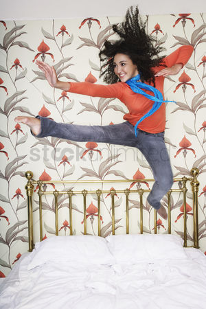 Arm raised : Teenage girl arms outspread kicking jumping on bed