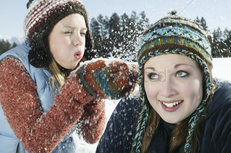Blowing : Teenage girl blows snow on her friend