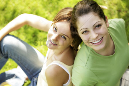 Outdoor : Teenage girls sitting on the field smiling at the camera